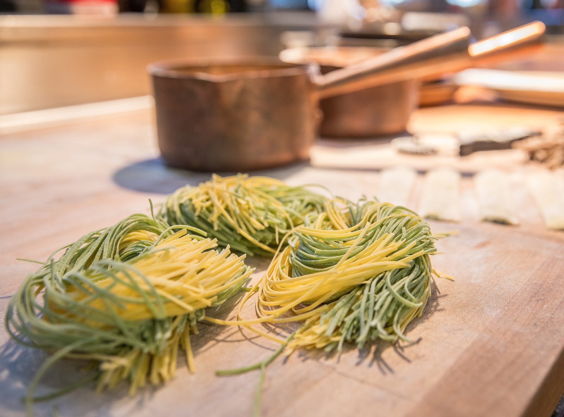 Close up of beautifully intertwined freshly made yellow and green pasta strips