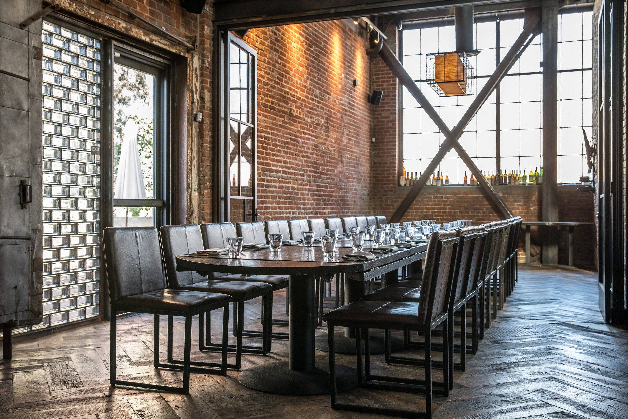 Inside Brera restaurant, industrial style, properly set dining table and comfortable leather chairs waiting to receive guests